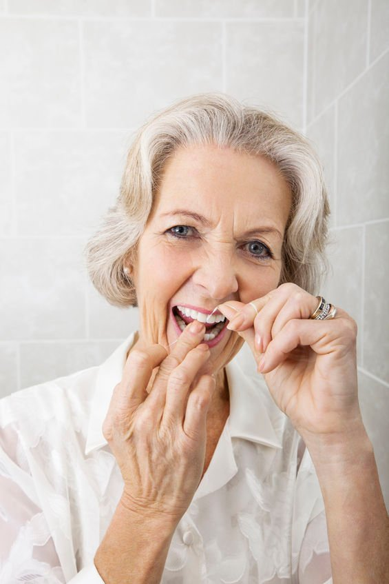 Senior woman flossing healthy teeth for life